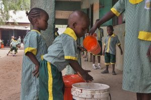On 17 March 2015, (left-right) a young girl waits her turn while a boy washes his hands with water that an older girl is pouring from a pitcher, after lunch at St Theresa Catholic School in Yola, capital of the north-eastern state of Adamawa, which has been affected by the escalating Boko Haram insurgency. The school is hosting students whose families have been displaced by the armed conflict. In March 2015 in Nigeria, 15.5 million people, including 7.3 million children, are affected by the continuing crisis in the country's north-eastern region. More than 1.2 million Nigerians have fled their homes as a result of violence and attacks by Boko Haram insurgents that have escalated since the beginning of 2015. Many of the displaced, most of whom are children and women, are sheltering with in host communities that have limited resources, and in formal and informal camps. All are in urgent need basic supplies, health and nutrition services, and critical water sanitation and hygiene support to prevent the spread of disease. Over 150,000 people,– the vast majority children and women – have also fled to neighbouring Cameroon, Chad and Niger, further straining vulnerable communities – some of which are already facing food insecurity and malnutrition, are prone to disease outbreaks and natural disasters, and often already host hundreds of thousands of refugees, returnees and migrants who have escaped violence and hardship throughout the region. The impact of the crisis on children and women is of particular concern. Many of them have lost their homes and belongings –escaping with only the clothing they were wearing; and some have walked for days – or even weeks – to find refuge. Many children in the region have been traumatized and are in need of psychosocial support. They have witnessed violence and atrocities, including seeing parents and siblings slaughtered by Boko Haram insurgents; and have been exposed to or have experienced violence and brutality. Thei