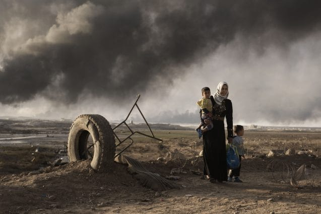 A newly displaced woman walks with two children at a check point in Qayyara, south of Mosul on October 31, 2016. On 17 November 2016, with one month of intensified military operations to retake the city of Mosul, tens of thousands of families in newly retaken areas urgently require life-saving assistance and the humanitarian community in Iraq faces a massive scope of need.  Nearly 59,000 people have been displaced, about 26,000 of them children. In support of the Government of Iraq, the United Nations and non-governmental organizations (NGOs) have begun to provide assistance to displaced and resident families in newly retaken areas. More than 40,000 displaced people have found shelter in formal camps in three governorates prepared and managed by the Government, the United Nations and national and international NGOs. More than half of the displaced people are women, girls, and female headed households who often are survivors of sexual and other human rights abuses.  More than 13,000 displaced people have been taken in by generous host communities or live in public facilities. More than 69,000 people have been given assistance within 48 hours of their displacement, more than 114,000 people have received food rations, more than 14,300 people have been provided with emergency health services and more than 66,000 people were provided with emergency household items and some 124,000 are receiving water, hygiene and sanitation services, including water trucking. Over 6,700 women and girls have received reproductive health consultations, including life-saving assisted deliveries. Some 1,400 sessions have been held to reach survivors of gender based violence. Shelter capacity and services in existing camps are being expanded and improved, and new emergency sites built.  More than 100 humanitarian partners are currently assisting people affected by the ongoing military operations according to the humanitarian principles of humanity, neutrality, impartiality and independe